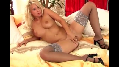 Busty blonde cutie in stockings fingers her pussy