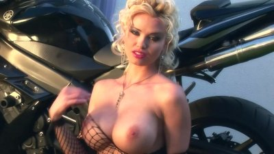 Busty Caylin teases on a motorcycle in a fishnet body stocking and boots