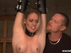 Blonde womens legs are spread wide by rope showing her bald cunt