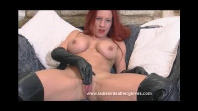 Busty red head Faye rubs her pussy with her leather gloves