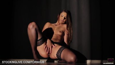 Artistic light on a perfect bodied beauty masturbating in stockings